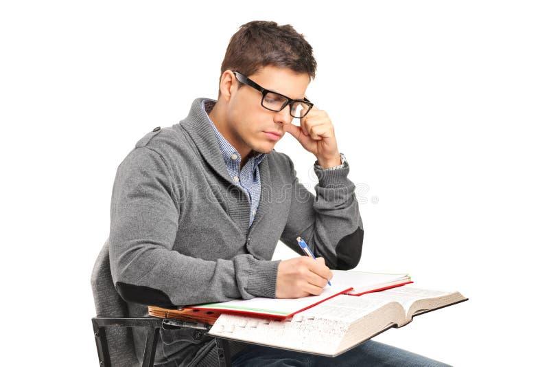 Een jong mannetje dat in gedachten een examen doet stock foto
