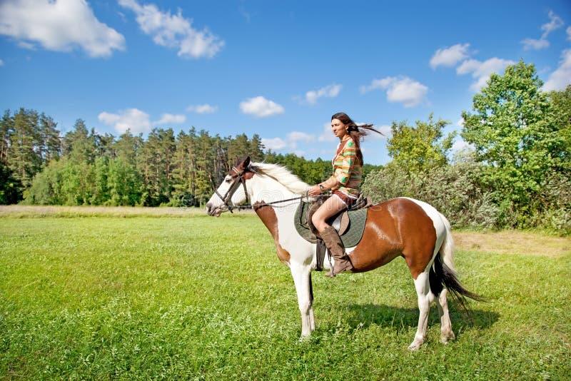 Een jong meisje berijdt een verfpaard royalty-vrije stock foto