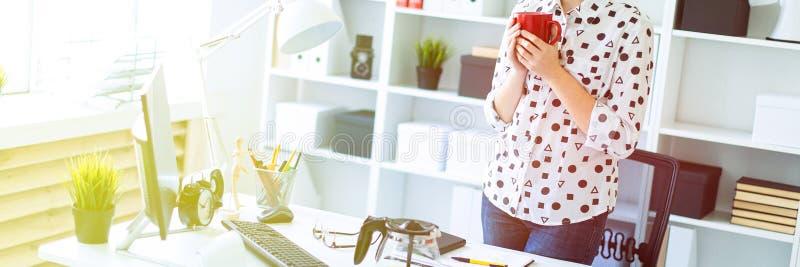 Een jong meisje bevindt zich in het bureau dichtbij de lijst, houdt een rode mok in haar handen en bekijkt de monitor stock afbeelding