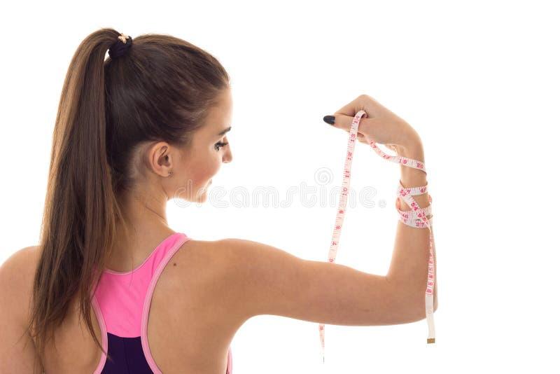 Een jong meisje bevindt zich onder ogen ziend die achteruit en houdt op hand een het meten bandclose-up op witte achtergrond word stock foto