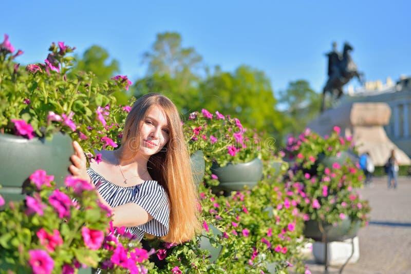 Een jong meisje bij de bloembedden op de achtergrond van monumen stock afbeeldingen