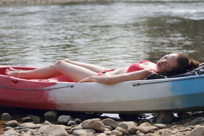 Een jong meisje in bikini die op de boot liggen en dichtbij de rivier, die van vakantie genieten in Laos zonnebaden stock afbeelding