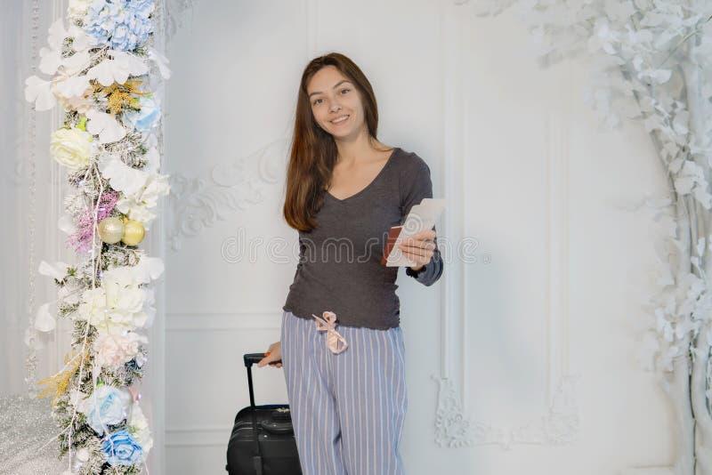 Een jong meisje in een bruin jasje met kaartjes en een paspoort in haar handen bekijkt de camera, glimlacht, draagt een koffer royalty-vrije stock afbeelding