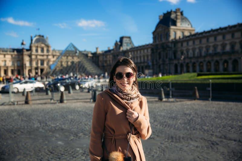 Een jong meisje in een bruine laag en een sjaal bevindt zich op de achtergrond van het Louvre De herfst is zonnig weer, toeristen royalty-vrije stock foto's