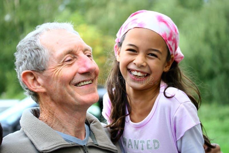 Een jong meisje dat een grap met haar grootvader deelt stock afbeeldingen