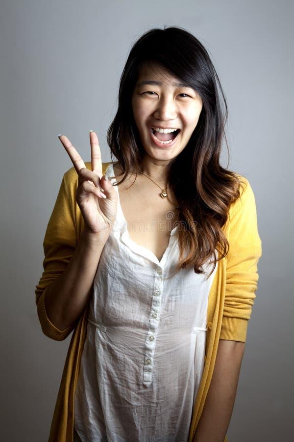 Een jong meisje dat een vredesteken maakt. stock foto's