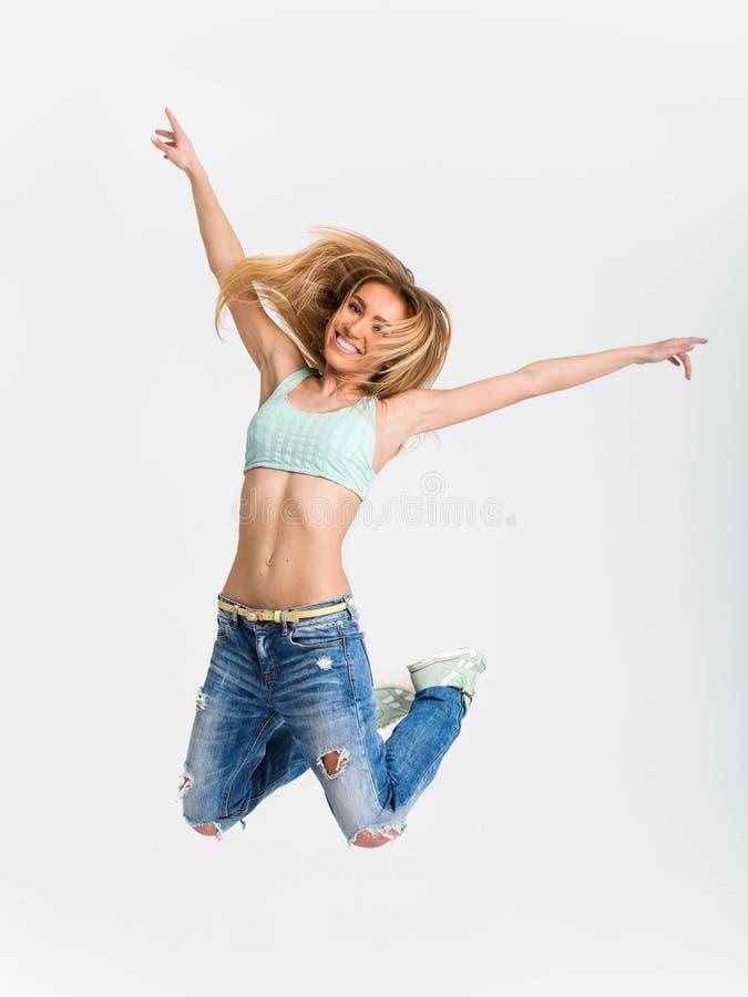 Een jong meisje die tegen witte studioachtergrond springen stock foto's