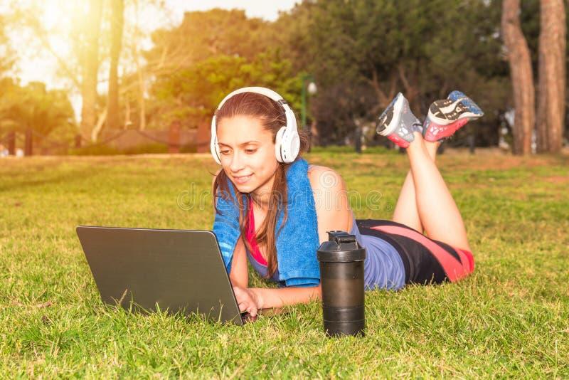 Een jong meisje in een park op het gras na geschiktheid opleiding met laptop en hoofdtelefoons royalty-vrije stock foto's