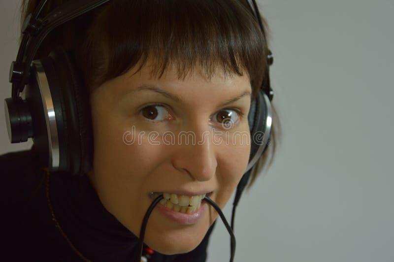 Een jong meisje, een vrouw met hoofdtelefoons en een microp stock afbeeldingen