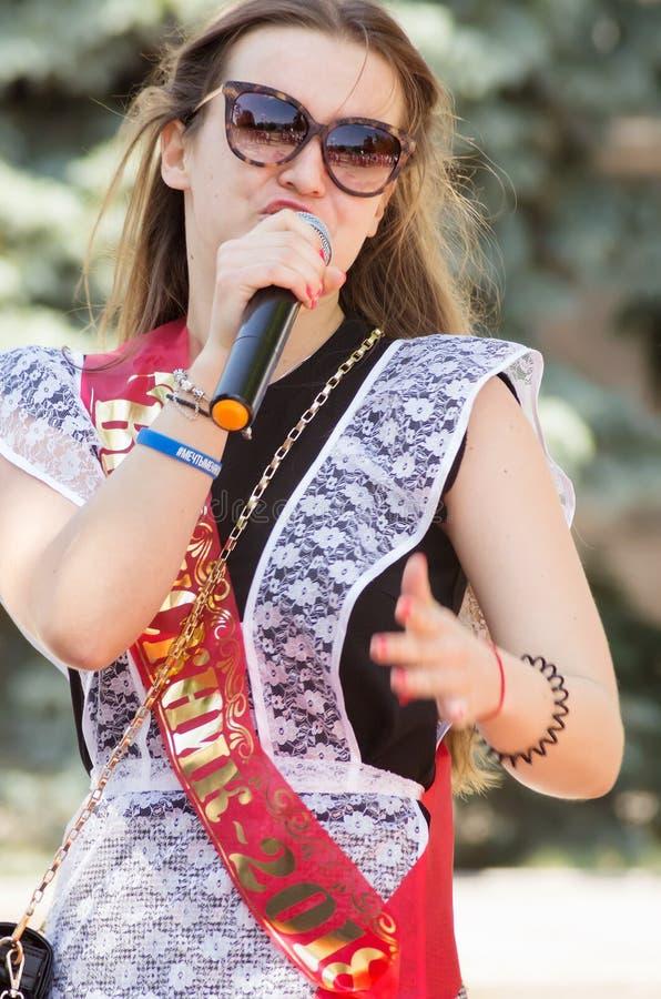Een jong meisje in een feestelijke eenvormige school, presterend bij de karaokeconcurrentie in een stadspark stock foto's