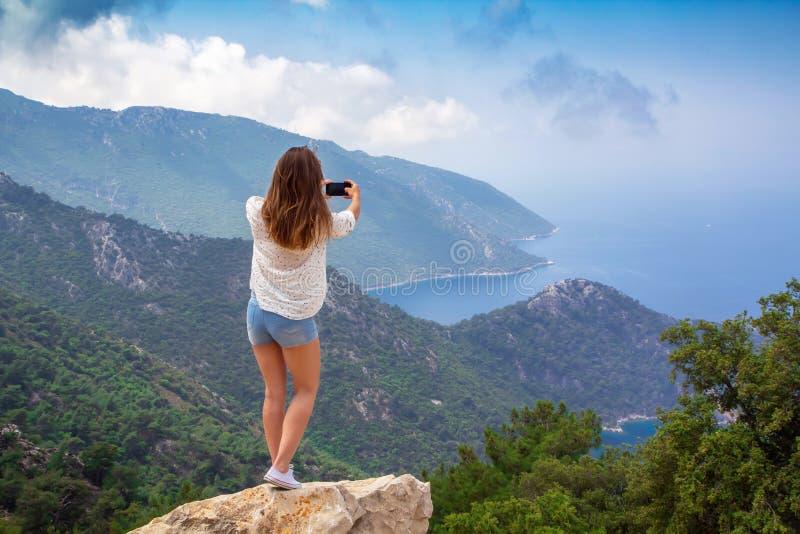 Een jong meisje fotografeert het landschap op een mobiele telefooncamera royalty-vrije stock foto