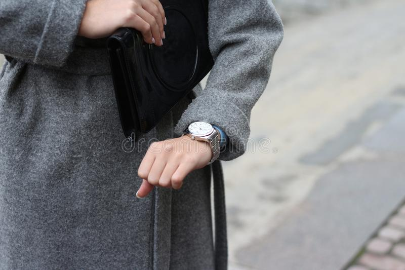 een jong meisje in een grijze laag bekijkt haar polshorloge, controleert de tijd, bekijkt haar horloge de haast aan een vergaderi royalty-vrije stock fotografie
