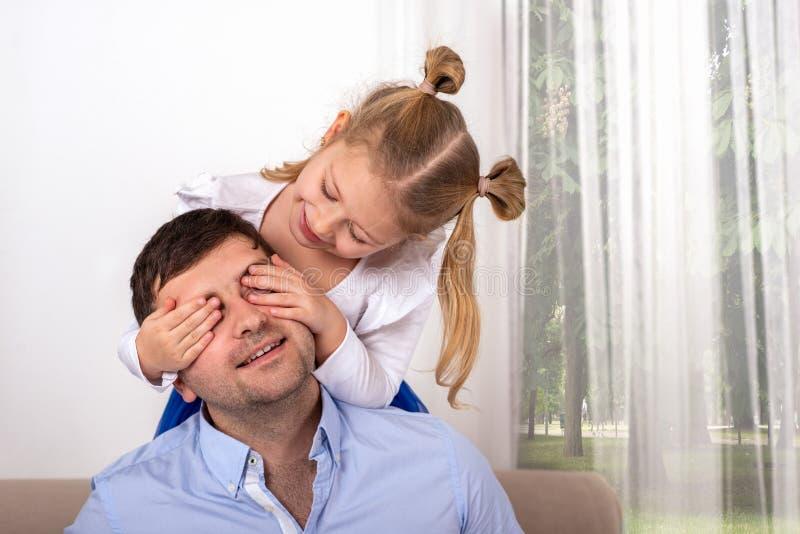 Een jong meisje heeft pret het spelen met haar papa, die zijn ogen sluiten zodat hij kan veronderstellen wie het is royalty-vrije stock foto's