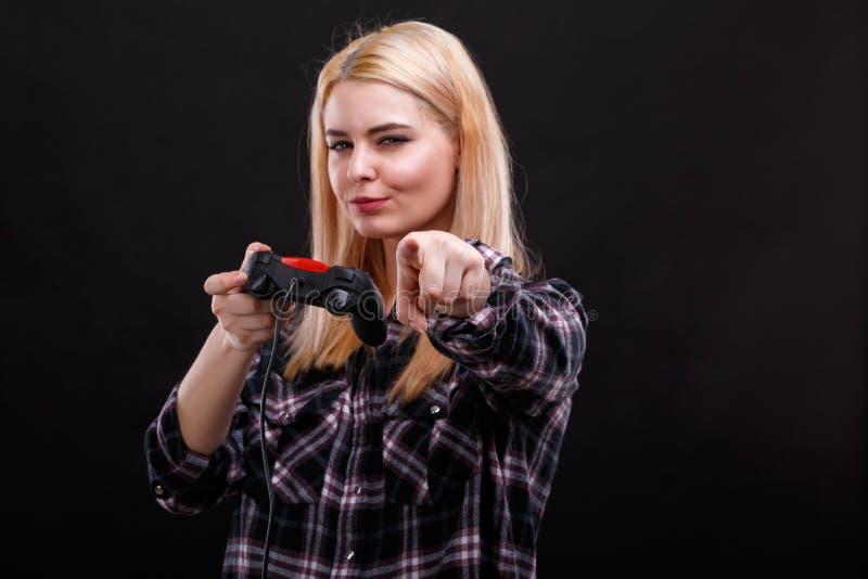 Een jong meisje, houdt een bedieningshendel en toont haar vinger voor haar stock foto's