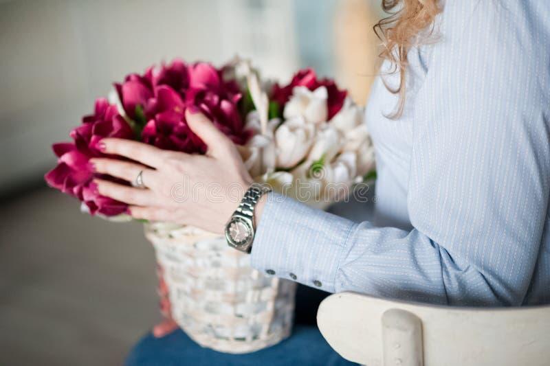 Een jong meisje houdt de lentebloemen in haar handen Een meisje en een boeket van mooie bloemen royalty-vrije stock afbeelding