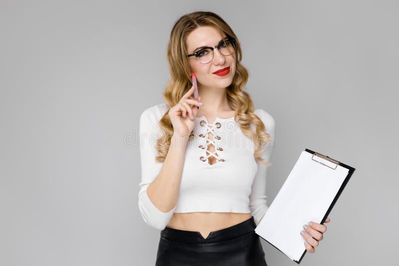 Een jong meisje houdt een pen en bladen voor nota's Portret van een blonde in een witte blouse en een zwarte rok royalty-vrije stock afbeelding