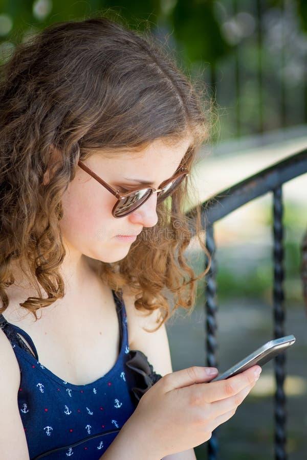 Een jong meisje houdt een telefoon in haar handen Mededeling die een smartphone gebruiken Modern vermaak op Internet_ royalty-vrije stock afbeeldingen