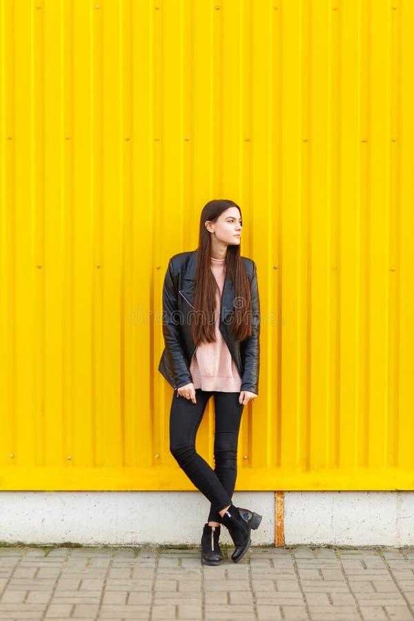 Een jong meisje, in een leerjasje, bevindt zich dichtbij de gele muur en kijkt weg stock afbeelding