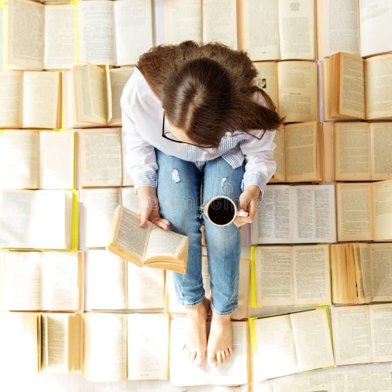 Een jong meisje leest een boek en drinkt koffie Hoogste mening Concept voor de Dag van het Wereldboek, levensstijl, studie, onder stock foto's