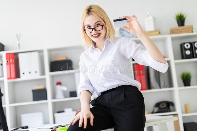 Een jong meisje leunde op het Bureau in het bureau en de holding een Betaalpas royalty-vrije stock fotografie