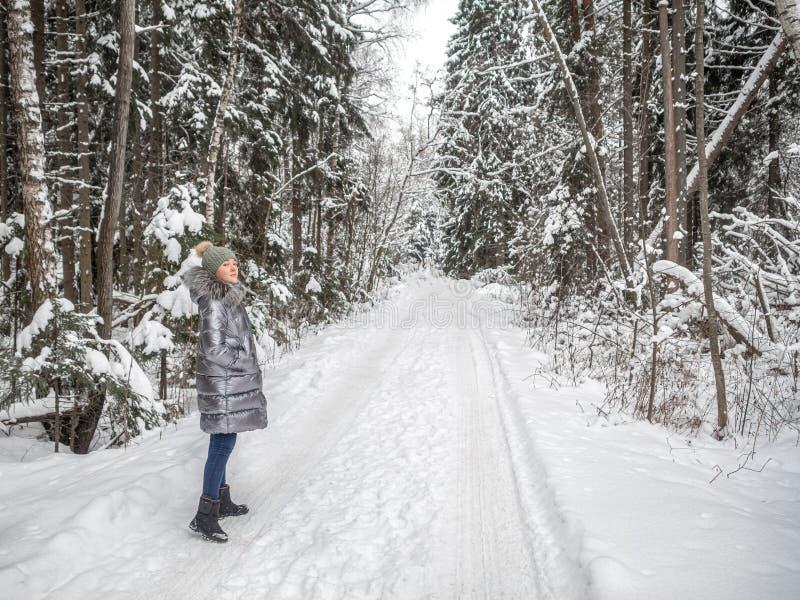 Een jong meisje loopt in het de winterbos en geniet van stilte stock fotografie