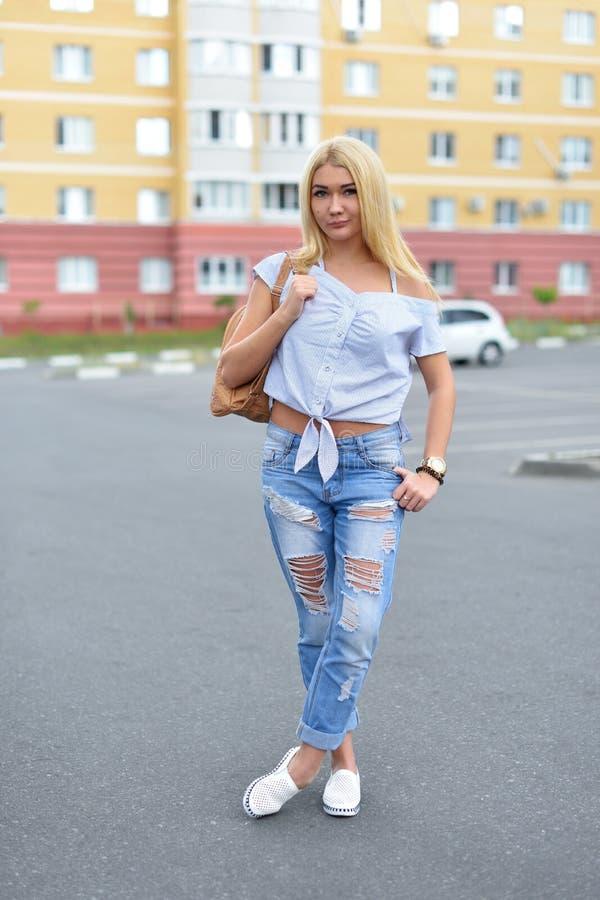 Een jong meisje loopt onderaan de straat met een beige rugzak in gescheurde jeans Modieuze gescheurde jeans op de benen van een t stock foto