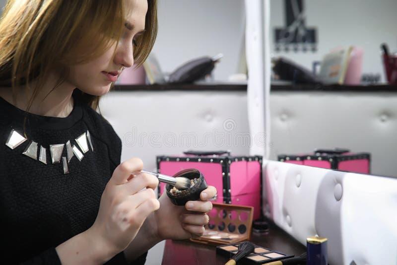 Een jong meisje maakt in een schoonheidssalon op Het meisje vooraan o stock foto's