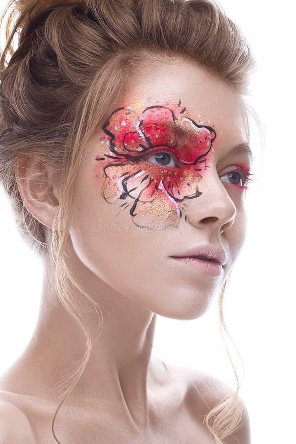 Een jong meisje met een creatieve make-up in de vorm van een rood-goudbloem op haar oog Mooi model in het beeld van een de lenteb stock afbeeldingen