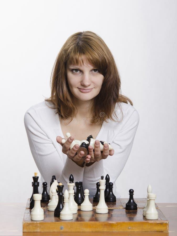 Een jong meisje met een handvol cijfers in de handen die bij de schaakraad zitten stock foto