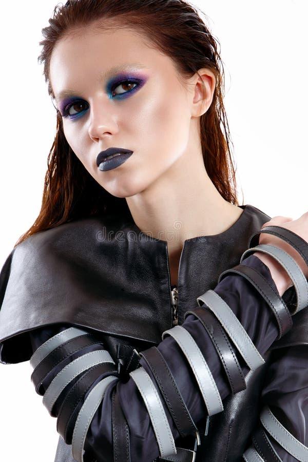 Een jong meisje met een heldere en heldere make-up in de stijl van gotisch Mooi model met glanzende huid en in een leerkostuum royalty-vrije stock afbeeldingen