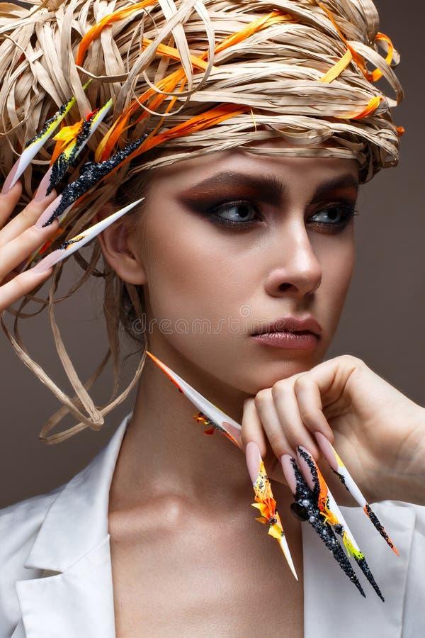 Een jong meisje met lange verfraaide spijkers en heldere creatieve make-up Mooi model met een strohoed op haar hoofd Mooie manicu stock afbeeldingen
