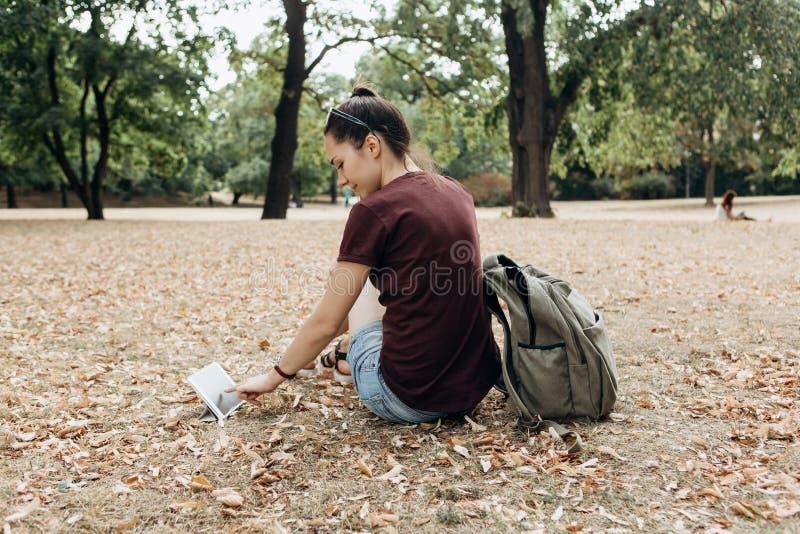 Een jong meisje met een rugzak zit in het de herfstpark en gebruikt de tablet stock afbeeldingen