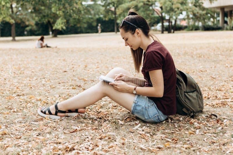 Een jong meisje met een rugzak zit in het de herfstpark en gebruikt de tablet royalty-vrije stock fotografie