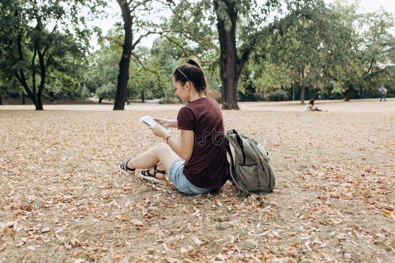 Een jong meisje met een rugzak zit in het de herfstpark en gebruikt de tablet royalty-vrije stock afbeeldingen