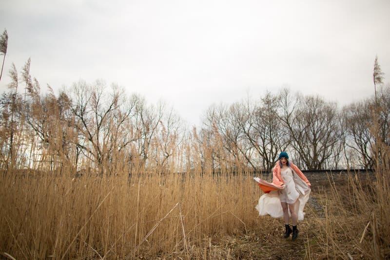 Een jong meisje in een mooie witte kleding en een modieuze hoed stelt op een tarwegebied royalty-vrije stock afbeeldingen