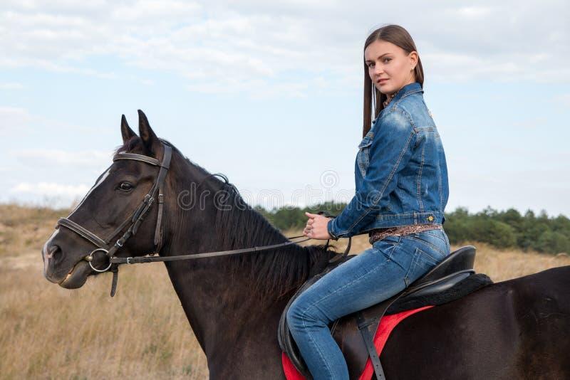 Een jong meisje op een donker paard royalty-vrije stock afbeelding