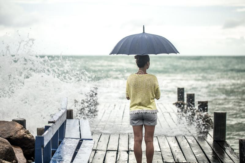 Een jong meisje op een pijler met een paraplu royalty-vrije stock foto's