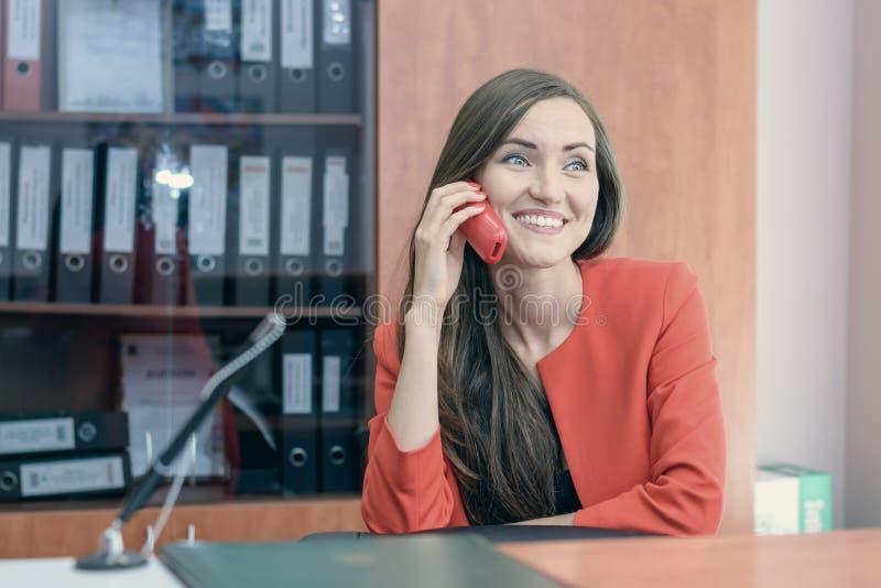 Een jong meisje in een rood kostuum leunt bij werk achterover, die op de telefoon met vrienden het spreken Het werk van het burea stock afbeelding
