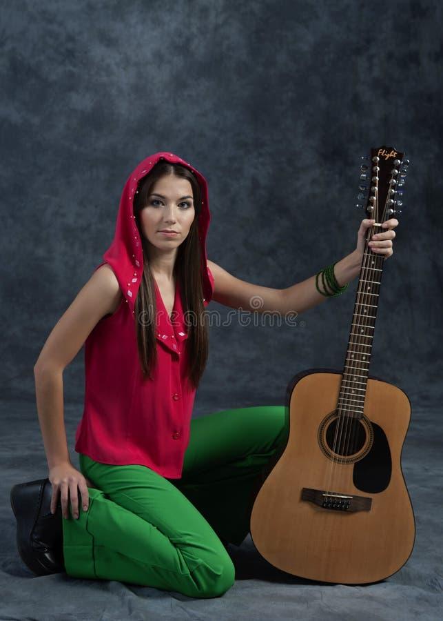Een jong meisje speelt de gitaar stock afbeeldingen
