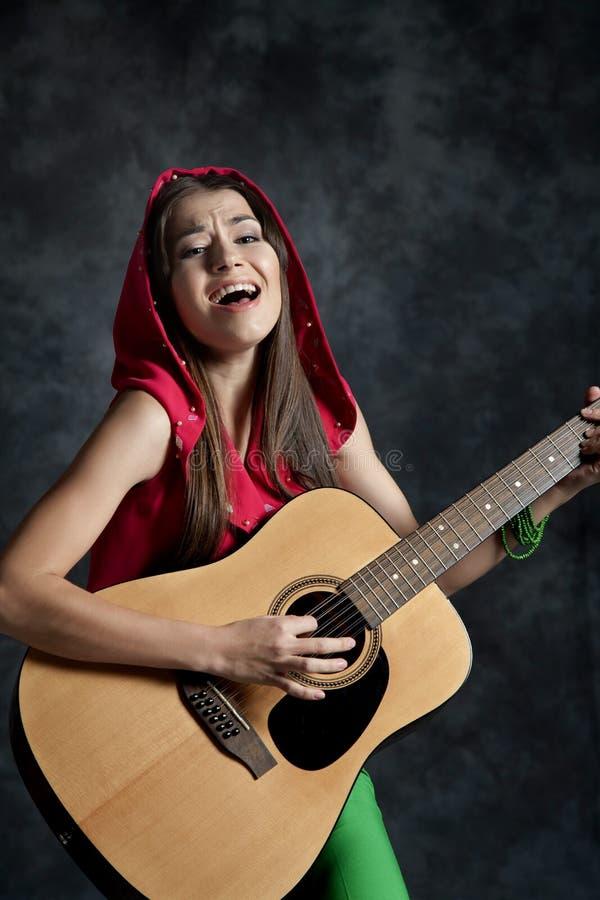 Een jong meisje speelt de gitaar stock foto's