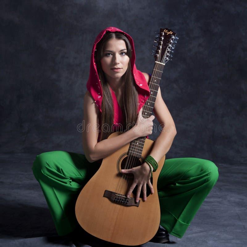 Een jong meisje speelt de gitaar stock fotografie