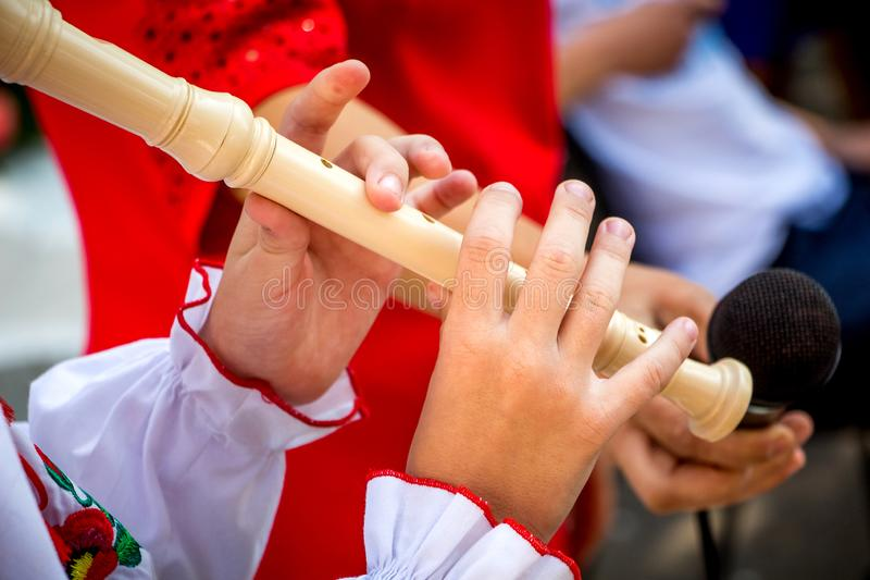 Een jong meisje speelt een houten fluit Het uitvoeren van muzikaal composit stock afbeelding