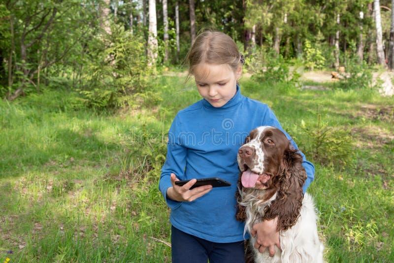 Een jong meisje toont iets aan haar hond in een mobiele telefoon Een kind speelt met een hond en een telefoon stock afbeelding