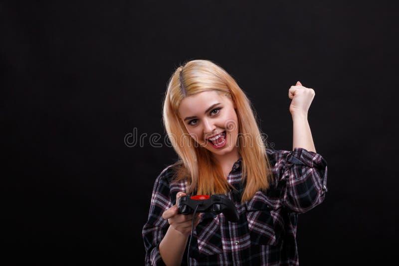 Een jong meisje verheugt zich en heft haar wapens op het houden van een spelbedieningshendel in op haar hand royalty-vrije stock fotografie