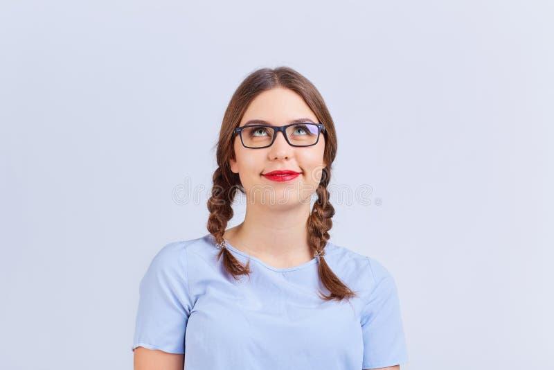Een jong meisje in vlechtglazen denkt, droomt met positief e stock foto's