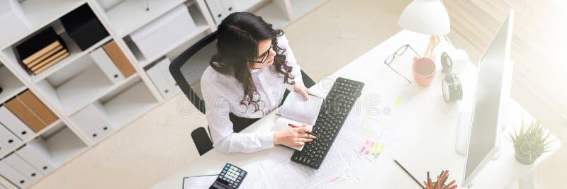 Een jong meisje werkt bij de computer in het bureau en houdt een pen en een notitieboekje in haar hand royalty-vrije stock afbeelding