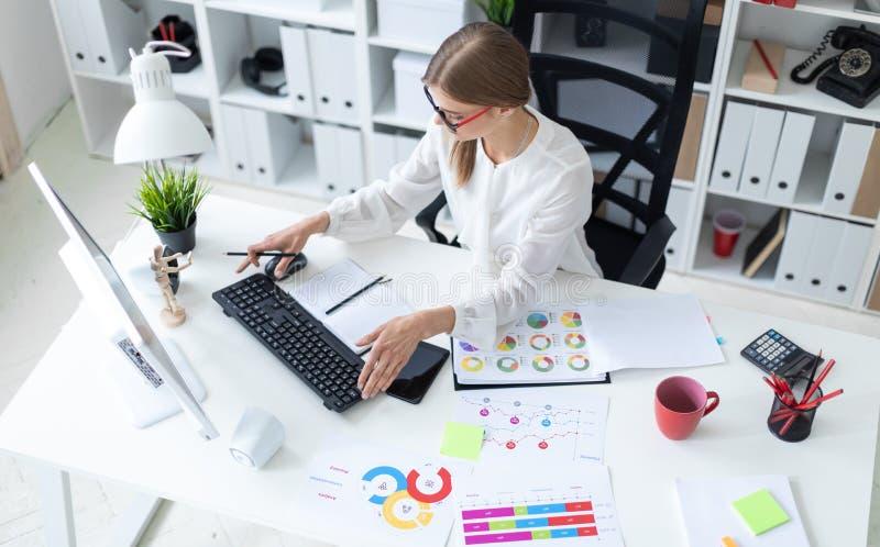 Een jong meisje zit bij een lijst in het bureau, houdt een potlood in haar hand en typt op het toetsenbord Vóór royalty-vrije stock foto's