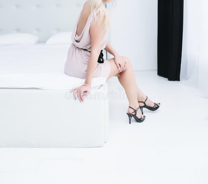 Een jong meisje zit in de slaapkamer op het bed in een witte kleding en hielen stock afbeelding