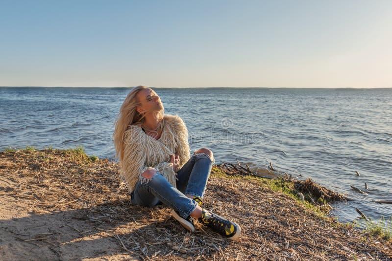 Een jong meisje zit het lounging op de kust van een vijver en de wind blaast haar blond haar royalty-vrije stock afbeelding