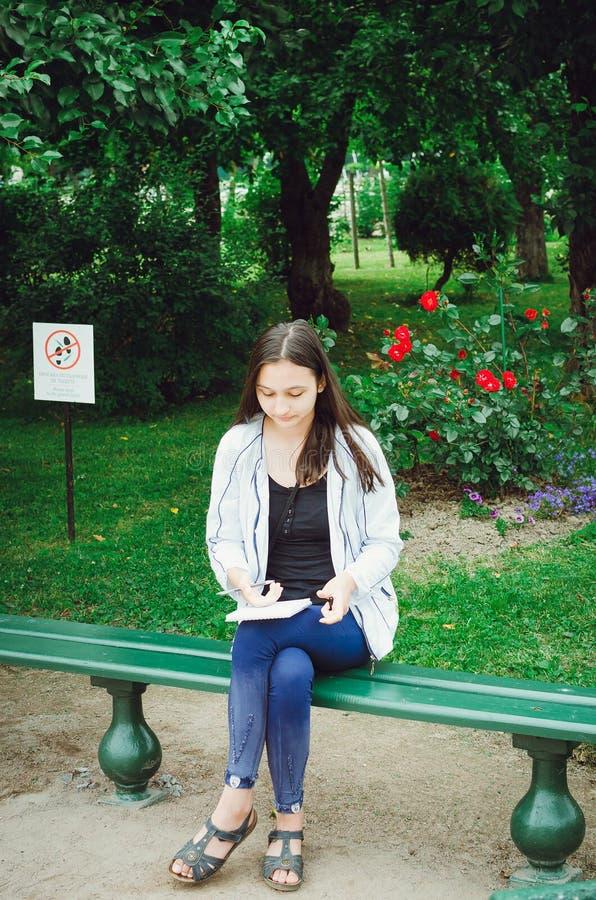 Een jong meisje zit op een bank in de tuin en trekt royalty-vrije stock fotografie